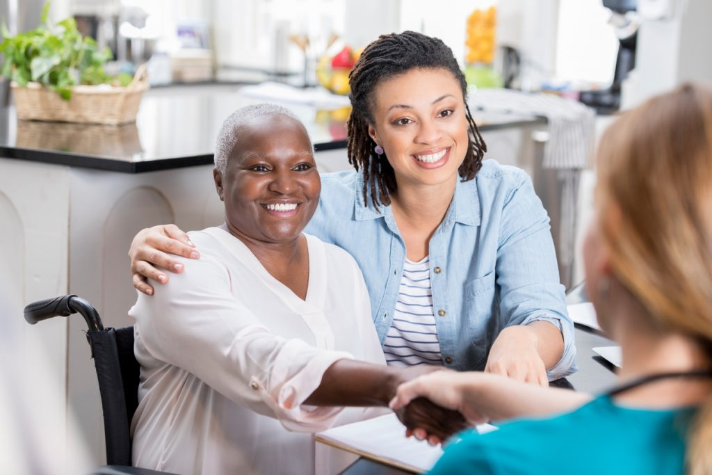 adult-daughter-and-her-senior-mother-meeting-with-care-provider-and-shaking-hands