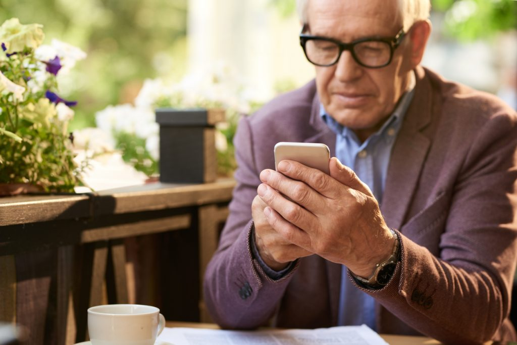 senior-man-wearing-glasses-and-sportcoat-using-smartphone-at-a-cafe-table-outdoors