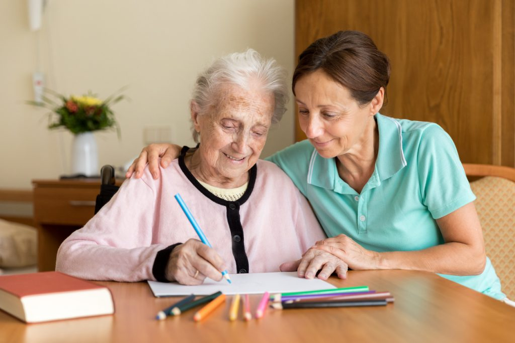 caregiver-with-arm-around-senior-woman-as-she-writes-with-pencil-on-paper