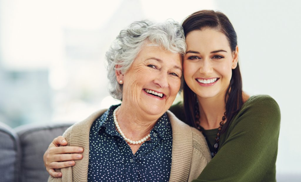 portrait-of-young-adult-woman-hugging-senior-female-relative-while-smiling