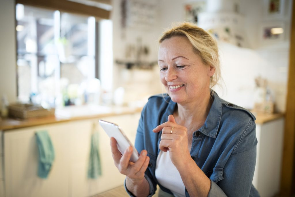 middle-aged-woman-with-blond-hair-smiling-while-using-smartphone-in-her-kitchen